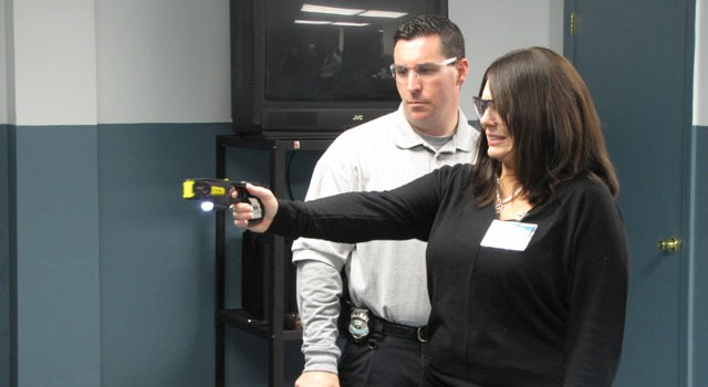Detective Douglas Cerce (L) demonstrates the Taser at the Smithfield PD Citizens Police Academy